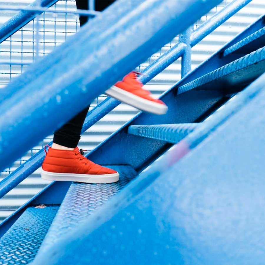 MM Steps of change orange sneakers climbing blue stairs