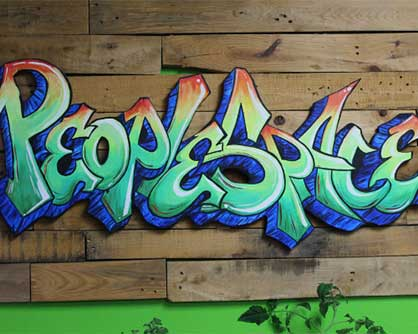 grafitti spelling peoplespace on a wooden wall