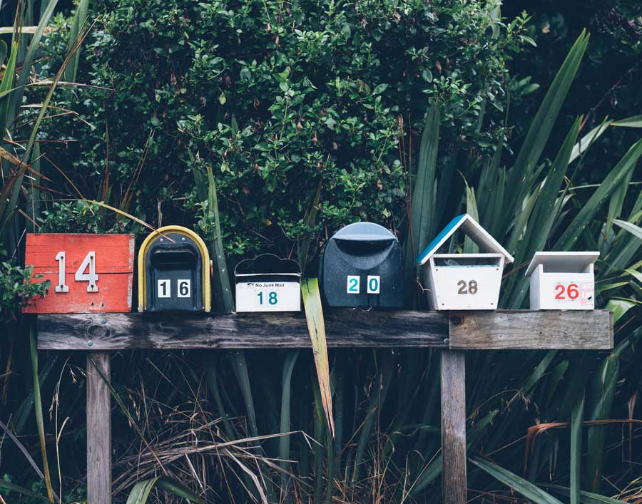 row of multi-colored mailboxes with foliage background