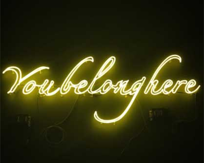 neon sign in the dark spelling out youbelonghere